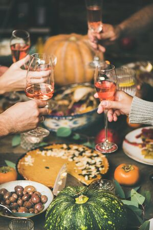 Traditional Christmas or New Year holiday celebration party. Friends or family feasting and clinking glasses with rose wine at festive table with variety of homemade snacks Stock Photo