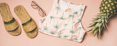 Summer apparel items. Flat-lay of summer flip flops, sunglasses, pink bikini top with palm pattern and pineapple over pastel pink background, top view, wide composition. Summer beach vacation concept