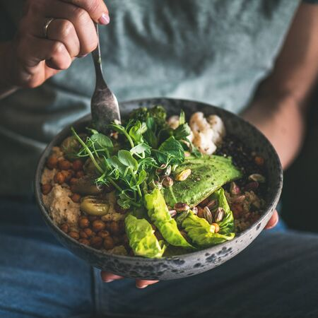Healthy dinner or lunch. Woman in t-shirt and jeans eating vegan superbowl or Buddha bowl with hummus, vegetable, salad, beans, couscous and avocado, square crop