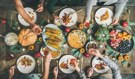 Wegańskie lub wegetariańskie Święto Dziękczynienia, Święto Przyjaciół. Płaskie ułożenie przyjaciół jedzących i ucztujących przy stole w Święto Dziękczynienia z ciastem dyniowym, warzywami, owocami i winem różanym, widok z góry Zdjęcie Seryjne