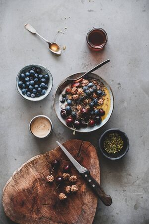 Healthy vegan breakfast. Flat-lay of quinoa oat granola coconut yogurt bowl with fresh fruit, seed, nut, berries and cup of coffee over grey background, top view. Clean eating, vegetarian food concept