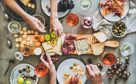 Midzomerpicknick met wijn en snacks. Flat-lay van charcuterie en kaasplank, rose wijn, noten, olijven en volkeren handen over betonnen tafel achtergrond, bovenaanzicht. Familie, vrienden vakantiebijeenkomst