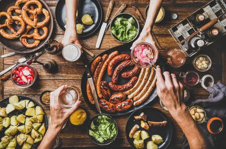 Flat-lay of Octoberfest party dinner table with grilled meat sausages, German pretzel pastry, potatoes, cucumber salad, sauces, beers and peoples hands with food over dark wooden background, top view