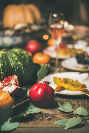 Traditional Christmas or New Year holiday celebration party. Rose wine and different snacks at festive Christmas table, selective focus, vertical composition