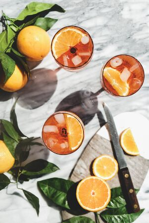alcohol cold drink in glasses with oranges and ice cubes over grey marble table, top view. Summer refreshing drink concept Stock Photo