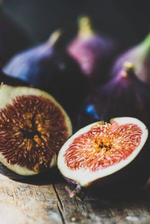 Fresh ripe seasonal harvested purple figs cut in slices over rustic wooden cutting board, selective focus, close-up