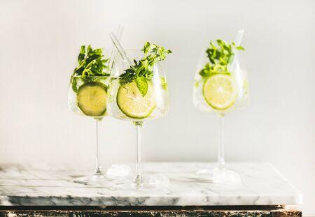 Hugo Sektcocktail mit frischer Minze und Limette in Gläsern mit umweltfreundlichen Strohhalmen über weißem Marmor, selektiver Fokus. Kaltes erfrischendes alkoholisches Sommergetränk Standard-Bild