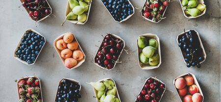 Summer fruit, berry assortment. Flat-lay of strawberries, cherries, grape, blueberries, pear, apricot, fig in eco-friendly boxes over grey background, top view, wide composition. Local farmers produce
