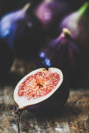 Fresh ripe seasonal harvested purple fig cut in slice over rustic wooden cutting board, selective focus, close-up Reklamní fotografie