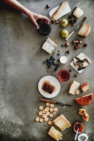 Wine snack variety. Flat-lay of cheeses, honey, fruit, nuts, crackers, wine in glass in female hand over grey concrete background, top view, copy space. Gathering, holiday, party food concept Reklamní fotografie