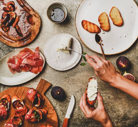 Party or catering food cooking. Flat-lay of crostini with prosciutto, grilled figs and womans hands spreading goat cheese on bread over grey concrete table background, top view
