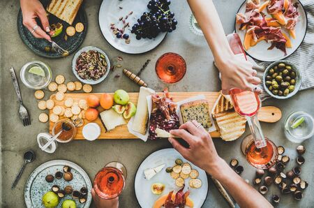 Mid-summer picnic with wine and snacks. Flat-lay of charcuterie and cheese board, rose wine, nuts, olives and peoples hands holding food and celebrating over concrete table background, top view Reklamní fotografie