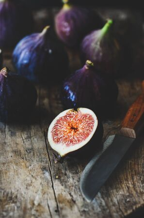 Fresh seasonal harvested purple figs over rustic wooden cutting board, selective focus, close-up Reklamní fotografie