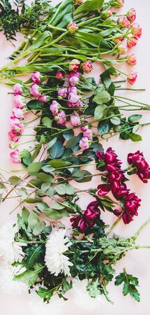 Various summer flowers flat-lay. Purple peonies, pink roses and tulips, white chrysanthemums and green branches with leaves over pastel pink background, top view Banco de Imagens - 129953322