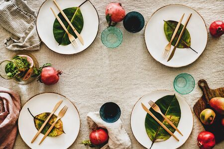 Fall or Autumn table setting for holiday dinner. Flat-lay of dinnerware with fruit and fallen leaves over linen tablecloth, top view, copy space. Preparation for Thanksgiving day or Christmas