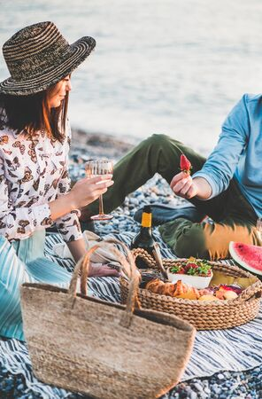 Summer beach picnic at sunset. Young couple having weekend picnic outdoors at seaside with fresh fruit and tray of tasty appetizers, drinking sparkling wine and eating strawberries