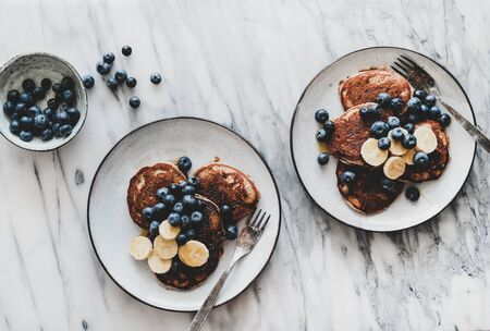 Healthy comfort breakfast set. Flat-lay of banana pancakes with fresh blueberry and honey in plates over white marble table