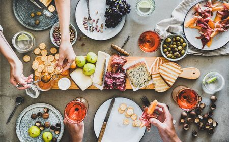 Mid-summer picnic with wine and snacks. Flat-lay of charcuterie and cheese board, rose wine, nuts, olives and peoples hands with snacks over concrete table background, top view Banco de Imagens - 130705480