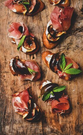Party or catering food. Flat-lay of crostini with prosciutto, goat cheese, grilled figs and fresh herbs on rustic wooden board background, top view, close-up Banco de Imagens