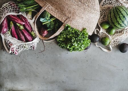 Eco-friendly lifestyle. Flat-lay of of grocery jute and net bags with fresh organic vegetables, greens, fruit from local farmers market, copy space. Zero waste, healthy, vegan and clean eating concept Banco de Imagens
