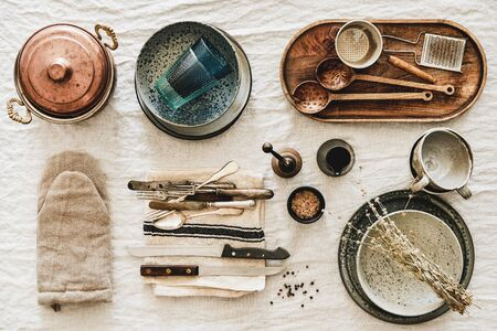 Flat-lay of various kitchen utensils, rustic tablewear, plates, dishes, glasswear, pan, mitten, textile for cooking over white rustic linen tablecloth background, top view. Seasonal cooking
