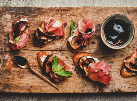 Party or catering food. Flat-lay of crostini with prosciutto, goat cheese and grilled figs on rustic wooden board over grey concrete table background, top view, close-up