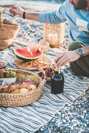 Summer beach picnic at sunset. Young couple sitting on blanket having weekend picnic outdoor at seaside with fresh seasonal fruit, tray of tasty appetizers and bottle of sparkling wine Banco de Imagens