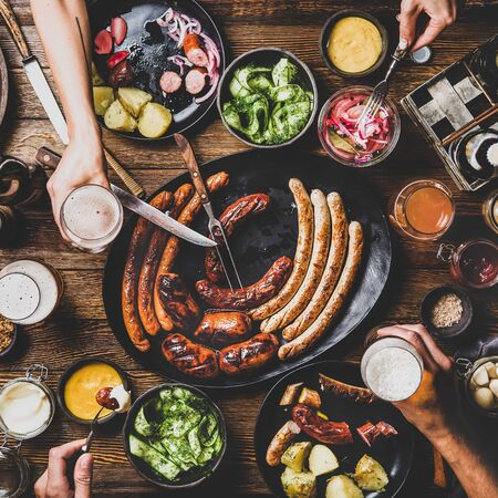 Flat-lay of Octoberfest dinner table with grilled sausages, pretzel pastry, potatoes, cucumber salad, sauces, beers and people drinking and eating over dark wooden background, top view, square crop