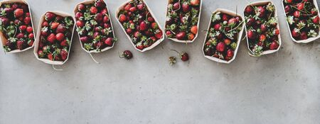 Fresh seasonal summer local market fruit produce. Flat-lay of garden harvest strawberries in eco-friendly plastic-free boxes over grey concrete background, top view, copy space, wide composition