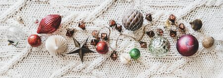 Christmas or New Year holiday background, texture, wallpaper. Flat-lay of Christmas festive decoration toys and balls over white knitted woolen background, top view, wide composition
