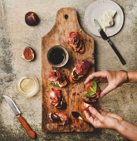 Party or catering food. Flat-lay of crostini with prosciutto, goat cheese and grilled figs on rustic wooden board and female hands holding canape over concrete background, top view Banco de Imagens - 131233189