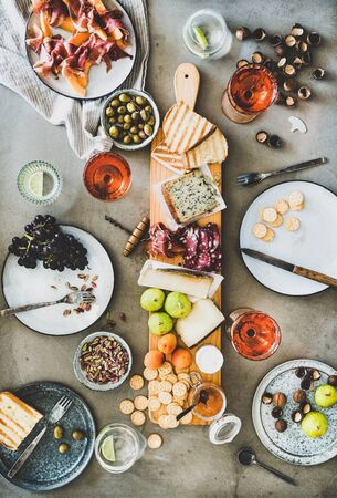Mid-summer picnic with wine and snacks. Flat-lay of charcuterie and cheese board, rose wine, nuts, olives and fruits over concrete table background, top view Banco de Imagens