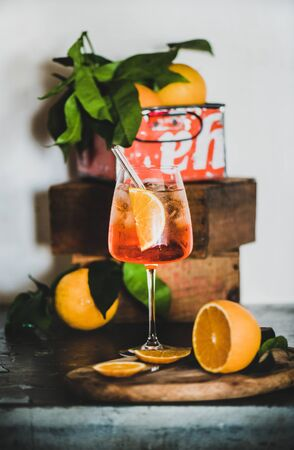 aperitif with oranges and ice in glass with eco-friendly glass straw on concrete table, white wall with boxes at background, selective focus, close-up. Summer refreshing drink concept