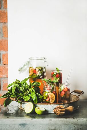 Fresh homemade strawberry and basil lemonade or ice tea in glass tumblers with eco-friendly plastic-free straws on rustic metal tray, white wall at background, copy space. Summer refreshing soft drink