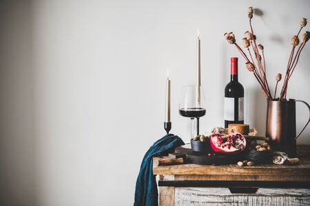 Wine and snack set. Glass and bottle of red wine, board with cheese, fruit, almonds and olives, candles and decorative flowers on kitchen counter, white wall at background, copy space. Winery concept