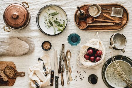 Flat-lay of various kitchen utensils, rustic tablewear, plates, dishes, glasswear, pan, mitten, fresh bread and seasonak red onion over white rustic linen tablecloth background, top view Banco de Imagens