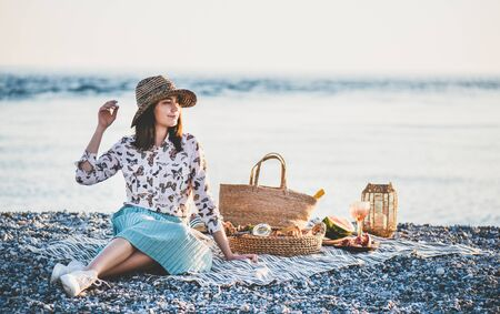 Summer beach picnic at sunset. Young woman in hat sitting on blanket and having weekend picnic outdoor at seaside with fresh seasonal fruit and tray full of of tasty appetizers