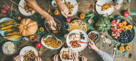 Thanksgiving or Friendsgiving holiday celebration party. Flat-lay of friends feasting at Thanksgiving Day table with turkey, pumpkin pie, roasted vegetables and fruit, top view, wide composition