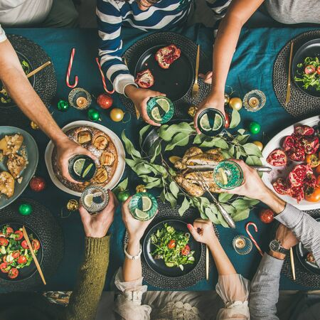 Company of friends gathering for Christmas or New Year party dinner at festive table. Flat-lay of hands holding glasses with drinks, feasting and celebrating holiday together, top view, square crop Banco de Imagens