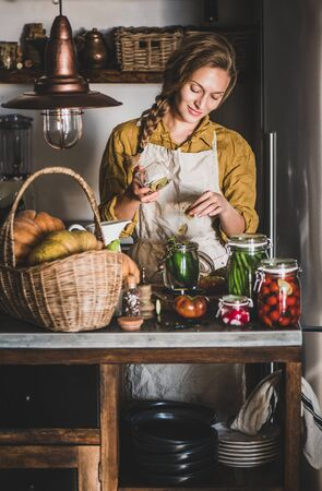 Autumn vegetable pickling and canning. Young blond woman in linen apron adding bay leaves to cucumbers and cooking homemade vegetables preserves in kitchen. Healthy organic fermented food concept Banco de Imagens