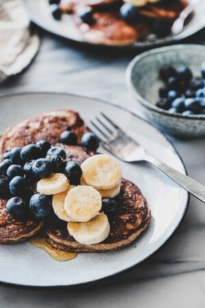 Healthy comfort breakfast set. Flat-lay of banana pancakes with fresh blueberry and honey in plates over white marble table background