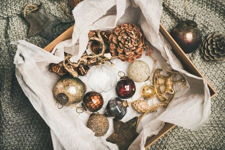 Christmas or New Year preparations. Flat-lay of various vintage Christmas tree decoration toys, balls and pine cones in wooden box over grey knitted background, top view. Festive holiday mood Banco de Imagens - 131217114