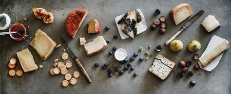 Wine snack variety. Flat-lay of cheeses, jam, fresh fruit, nuts and crackers over rough grey concrete background, top view, wide composition. Gathering, party, holiday food concept