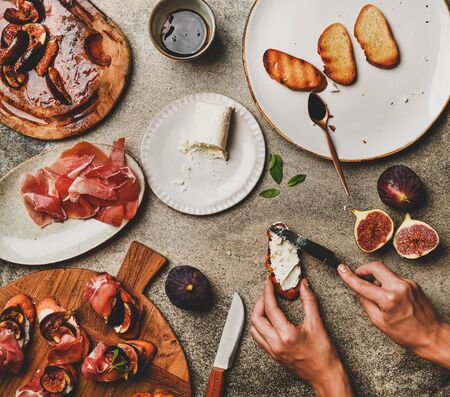 Party or catering food cooking. Flat-lay of crostini with prosciutto, grilled figs and female hands spreading goat cheese on bread over grey concrete table background, top view