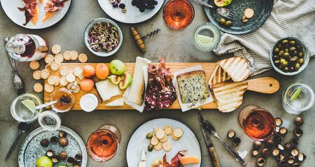 Mid-summer picnic with wine and snacks. Flat-lay of charcuterie and cheese board, rose wine in bottle and glasses, nuts, olives and fruits over concrete table background, top view, wide composition