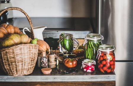 Autumn vegetable pickling and canning. Fresh ingredients and glass jars with homemade vegetables preserves on kitchen counter, close-up. Healthy organic fermented food concept