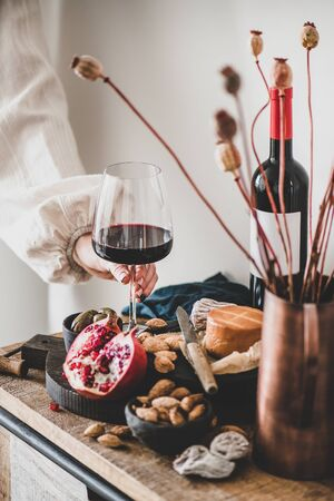 Red wine, board with cheese, fruit, almonds and olives, decorative flowers on kitchen counter and womans hand holding glass of wine, white wall at background. Wine tasting, wine bar concept