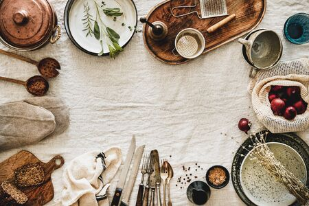 Flat-lay of various kitchen utensils, rustic tablewear, plates, dishes, glasswear, pan, mitten, textile for cooking over white linen tablecloth background, top view, copy space. Seasonal cooking Banco de Imagens - 131282841