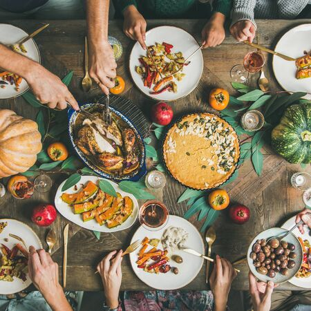 Thanksgiving or Friendsgiving holiday celebration party. Flat-lay of friends feasting at Thanksgiving Day table with turkey, pumpkin pie, roasted vegetables, fruit and rose wine, top view, square crop