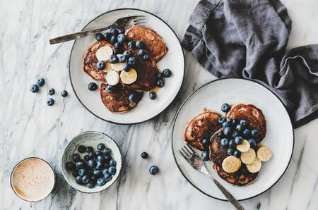 Flat-lay of banana pancakes with fresh blueberry and honey and cup of coffee over white marble table background, top view. Healthy comfort breakfast set